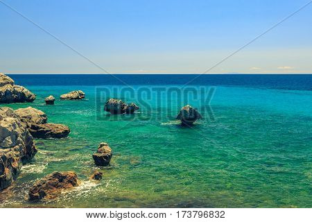 The Rocky Coast Overlooking The Turquoise Blue Sea In Warm Summer Day
