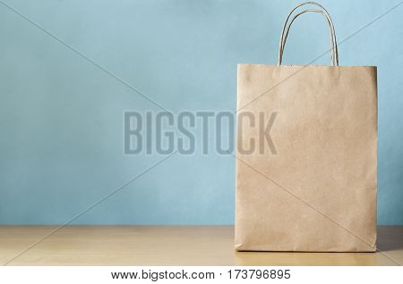Blank brown paper carrier bag with handles for shopping facing front on right side of a light wood veneer table with pale blue wall background providing copy space to left.