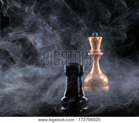 chess rook and queen in fog on black background