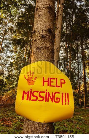 help the missing sign hanging on a tree woods / a sign reading help missing