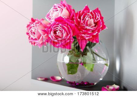 bouquet of pink roses in a glass bottle on a grey background