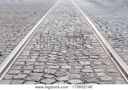 Old rail lines on cobbled road surface