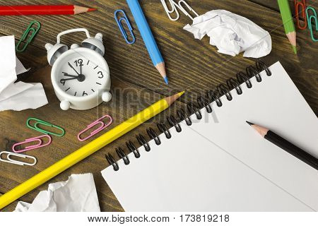 throes of creation, all drawing, colored pencils and paper clips notebook with an alarm clock on the table