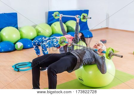 Girls in tracksuits lying on fitness balls doing barbell chest press in a gym. Two young women exercising indoors