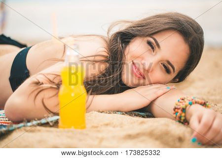 Beach woman drinking cold drink beverage having fun at beach party. Female babe in bikini enjoying orange water from glass boutle. summer concept