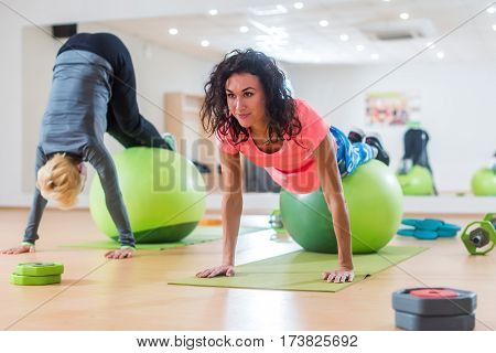 Attractive smiling slim young women training indoors doing pike rolls and handstand exercise with a Swiss ball on mats in fitness studio.