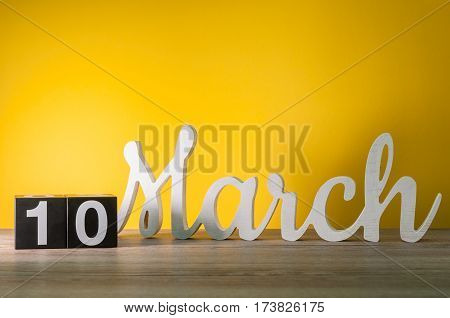March 10th. Image of march 10 wooden color calendar on white background. Spring day, empty space for text.