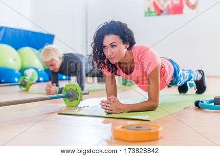 Sporty attractive young females doing yoga forearm planking exercise or Dolphin pose on mats while training in fitness club.
