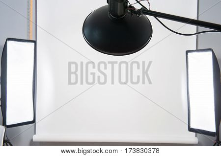 White studio backdrop with studio lights, two stip boxes and one beauty dish