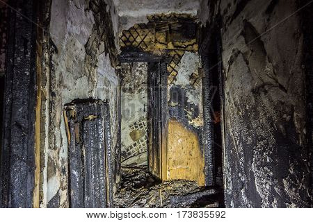 Interior of the burned by fire house, burned door in corridor