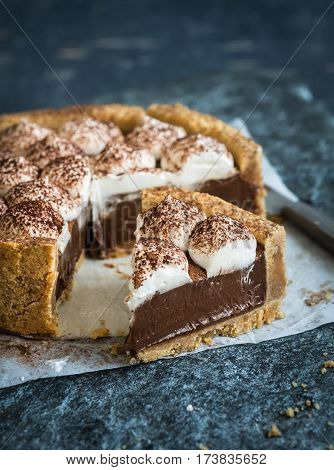 No bake duce de leche tart with chocolate and whipped cream,sprinkled with cocoa