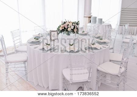 Well decorated guest numbered table in tenderless wedding hall, which is in white and silver colours