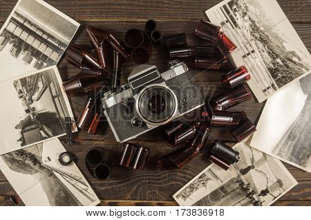 Old camera film and black and white photographs are on the dark wooden surface. Retro. Top view