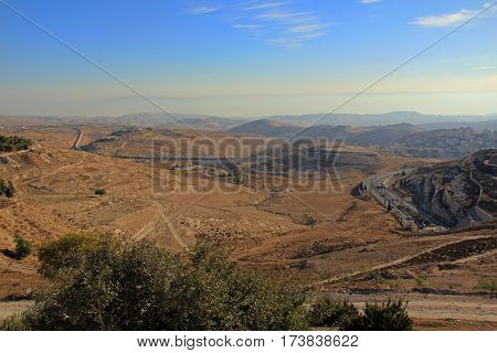 Judean desert wilderness as seen from Mt. Scopus in Jerusalem, Israel with smoky hazy mountains and buildings in the background,