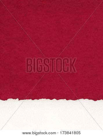 A section of deckled edge paper on a textured red background.