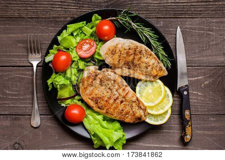 Grilled chicken breast fillet served with herbs vegetables and lemon on a plate. top view