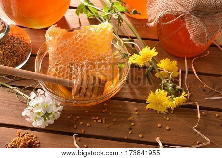 Honey Pots With Honeycomb On Wood Table Top Elevated View