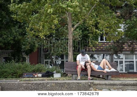 BELGRADE SERBIA - AUGUST 2 2015: Lovers resting on a bench a homeless sleeping in the background district of Zemun Belgrade