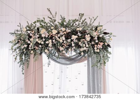 Beautiful wedding archway. Arch decorated with peachy and silvery cloth and flowers, in wedding hall