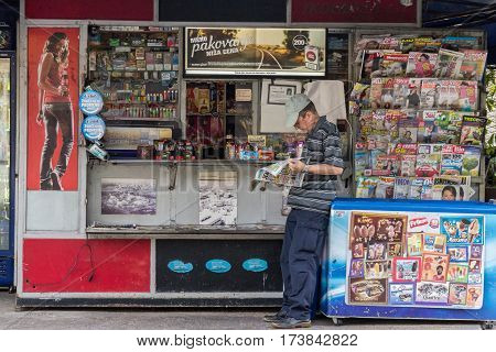 BELGRADE SERBIA - AUGUST 2 2015: Old man reading a newspaper at a kiosk (Trafika) in summer in the capital city of Serbia.