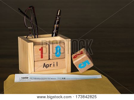 Wooden letters in calendar with Form 1040 income tax for 2016 showing tax day for filing is April 18 2017 instead of the normal 15th. Number 5 is shown falling to table