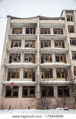 Winter, blizzard, snow, old ruined five-storey building with broken windows, the concept of loneliness and despair