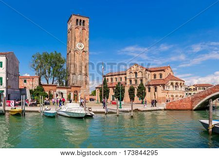 MURANO, ITALY - AUGUST 26, 2016: Narrow canal, church and tall belfry with clock in Murano - small island in Venetian lagoon, popular tourist destination, famous for its glass making.