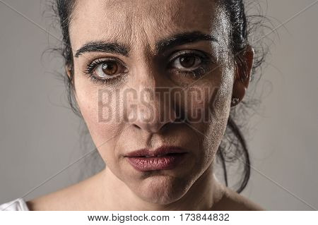beautiful face of sad woman crying desperate and depressed with tears on her eyes suffering pain and depression isolated on grey background in sadness facial expression and emotion concept