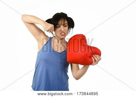 young attractive and beautiful woman punching in rage spiteful and resentful a red heart shape pillow upset and angry isolated background in love pain and romantic relationship broken concept