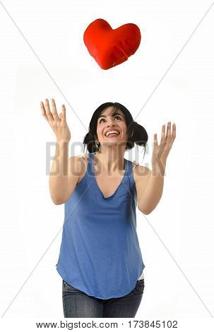young attractive and beautiful woman smiling happy feeling in love throwing to air red heart shape pillow looking sweet isolated on white in romantic female and valentines day celebration concept