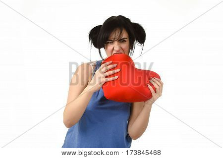 young attractive and beautiful woman biting in rage spiteful and resentful a red heart shape pillow upset and angry isolated background in love pain and romantic relationship broken concept