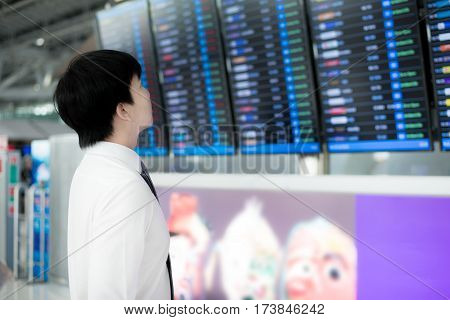 Asian young business man with luggage waiting for travel in airport near flight timetable. Business travel concept