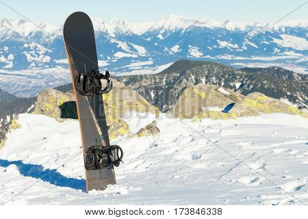Snowboard thrusted into snow at the top of a mountain - outdoors shot