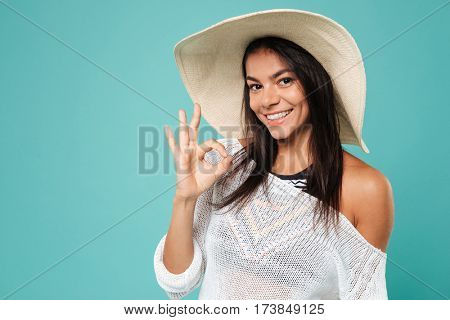 Picture of happy young lady wearing hat posing over blue background while make okay gesture.