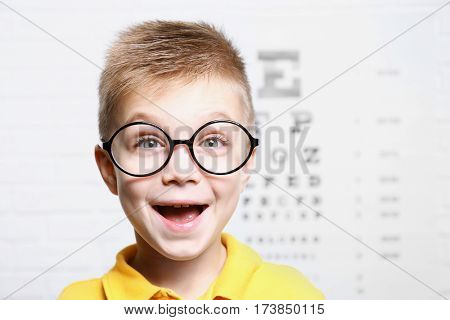 Little boy with spectacles on ophthalmic test chart background