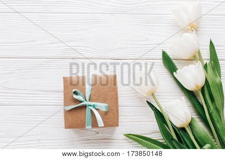 Stylish Craft Present Box And Tulips On White Wooden Rustic Background. Flat Lay With Flowers And Gi