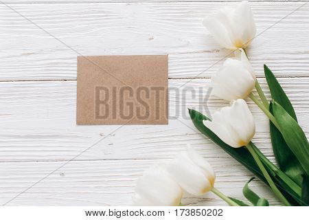 Stylish Craft Greeting Card And Tulips On White Wooden Rustic Background. Flat Lay With Flowers And