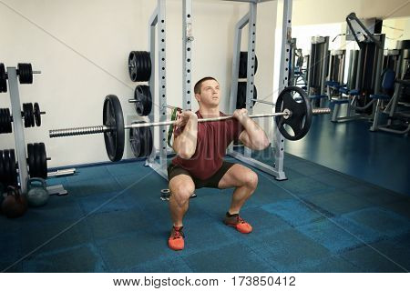Young handsome man with barbell training in gym