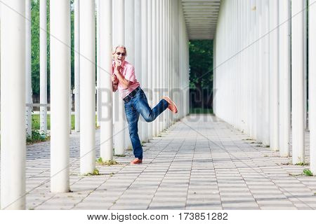 Senior man standing in white pillar hallway, pin-up-girl pose
