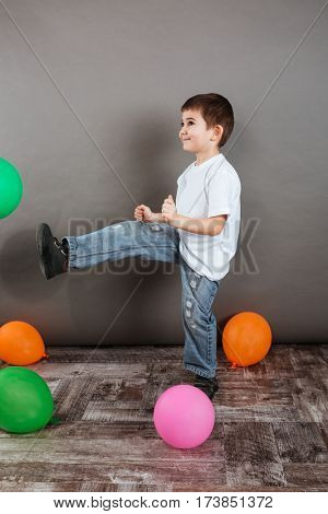 Happy little boy playing with colorful balloons and having fun