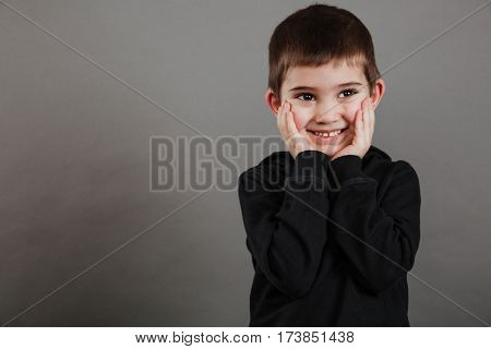 Shy happy little boy standing with hands on cheeks