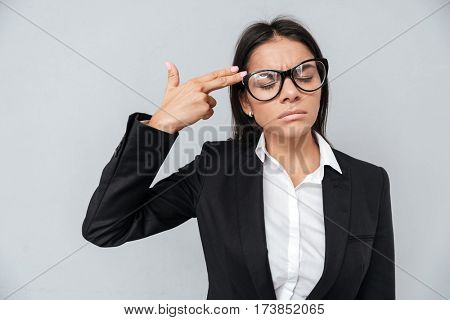 Business woman in suit and eyeglasses which showing gun sign near the head. Isolated gray background