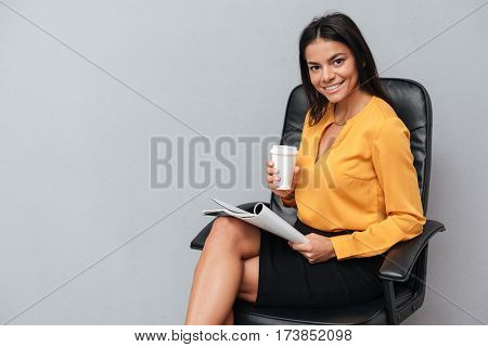 Portrait of a smiling young buisiness woman reading newspaper and drinking coffee while sitting on a chair isolated on a gray background