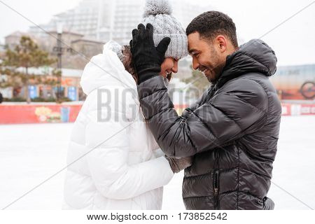 Photo of young happy loving couple skating at ice rink outdoors. Looking each other.