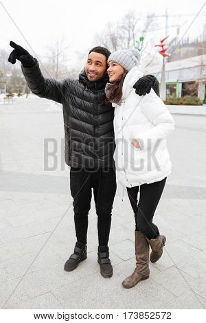 Happy multiethnic young couple standing and pointing away at winter park