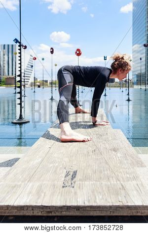 Woman doing yoga near lake in urban setting, La Defense, Paris