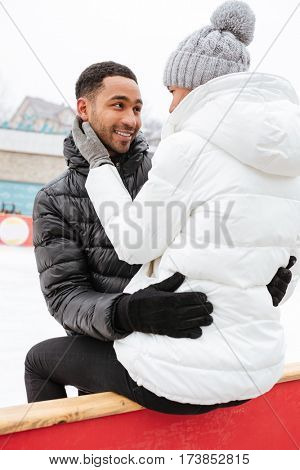 Happy multiethnic young couple in love hugging at outdoor rink