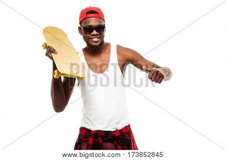 Smiling african young man holding skateboard and showing thumbs up over white background