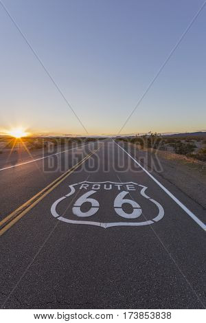 Route 66 pavement sign and Mojave Desert sunset in Southern California.