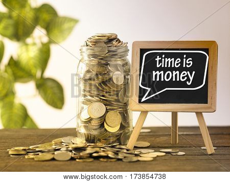 saving jar full of coins and mini blackboard with text time is money